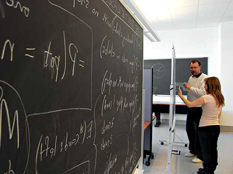 Student and professor work on a math problem on a chalkboard